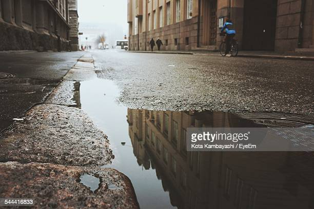 Reflection Of Building On Puddle