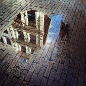 Reflection of buildings and columns in puddle