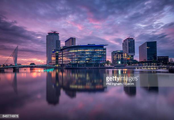 Reflection Of Buildings In Calm Water At Sunset