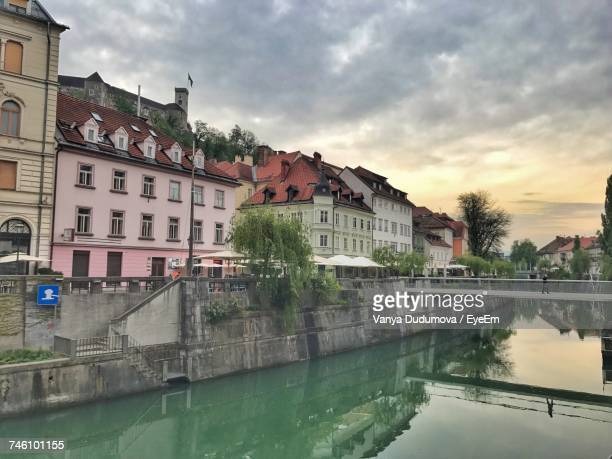 Reflection Of Buildings In Canal Against Cloudy Sky