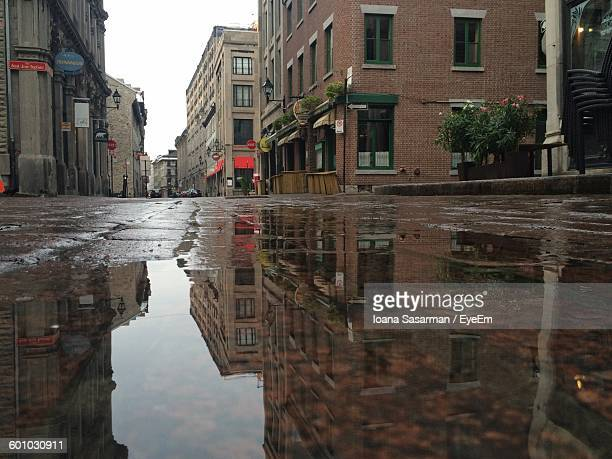 Reflection Of Buildings On Puddle In City