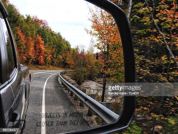 Reflection Of Car On Road By Autumn Trees On Side-View Mirror