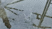 Reflection Of Chainlink Fence In Puddle During Rainy Season