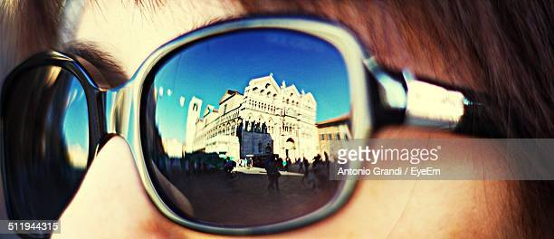 Reflection of church on sunglasses worn by woman