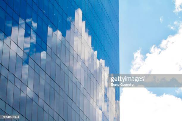 Reflection of clouds and sky on modern glass building