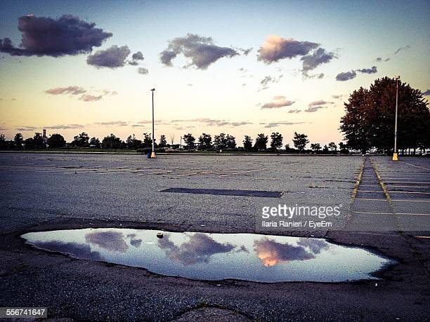 Reflection Of Clouds In Puddle On Parking Lot