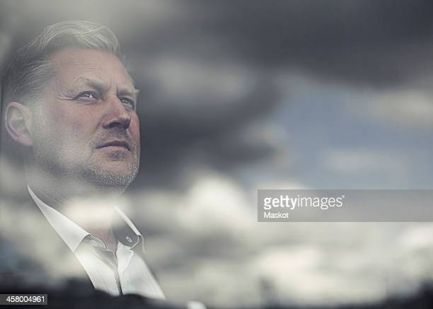 Reflection of clouds on glass window while businessman looking away