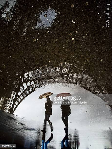 Reflection Of Eiffel Tower And Two People In Puddle Water