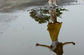 Reflection of girl dancing in puddle