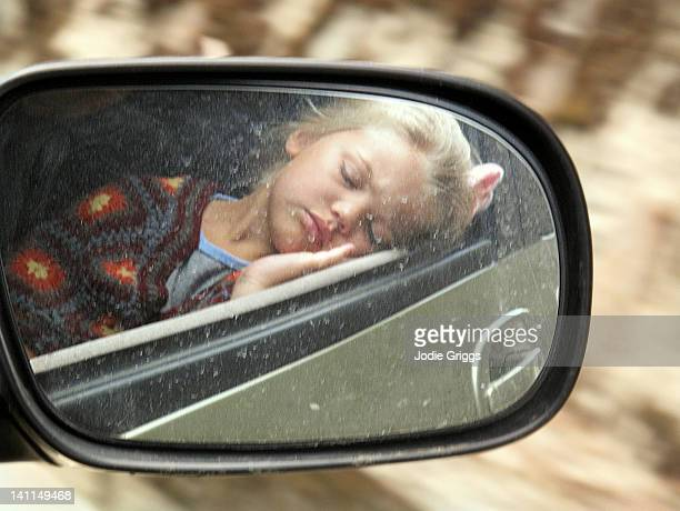 Reflection of girl sleeping on car side view mirr