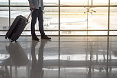 Reflection of half male body walking in the airport terminal with suitcase luggage, travel background with copy space
