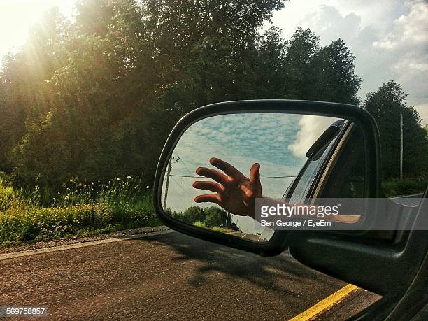 Reflection Of Hand On Side-View Mirror