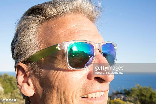 Reflection of hiker in man's sunglasses