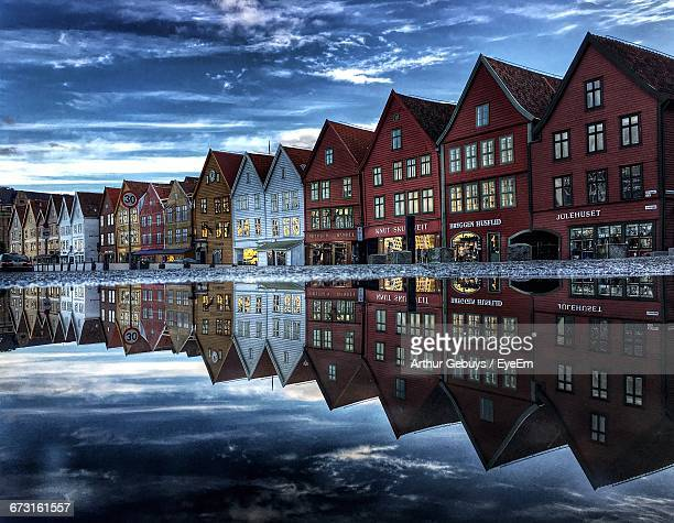 Reflection Of Houses On Water Against Sky