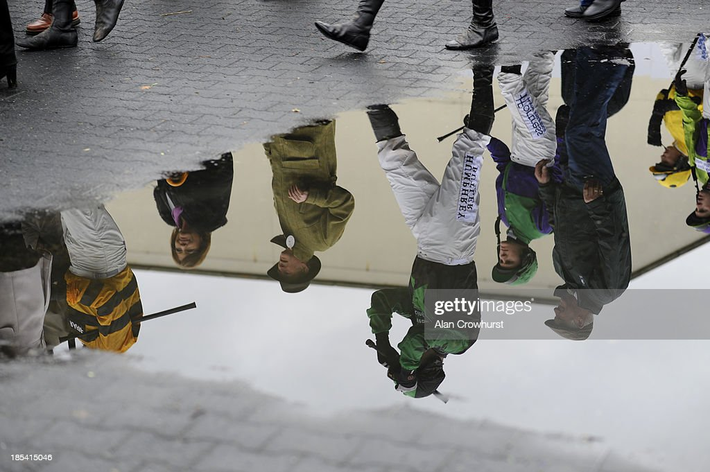 A reflection of jockeys and connections in a puddle on a wet day at Kempton Park racecourse on October 20, 2013 in Sunbury, England.
