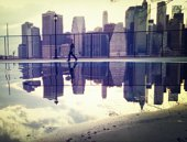 Reflection of man and urban building in puddle