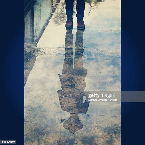 Reflection Of Man In Puddle