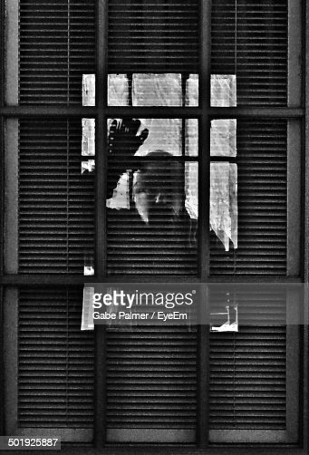 Reflection Of Man Looking Through Window On Blinds Stock