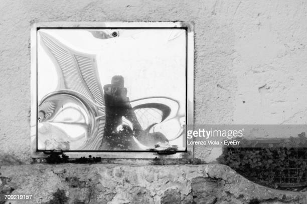 Reflection Of Man On Mirror At Wall