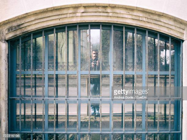 Reflection Of Man Photographing On Window