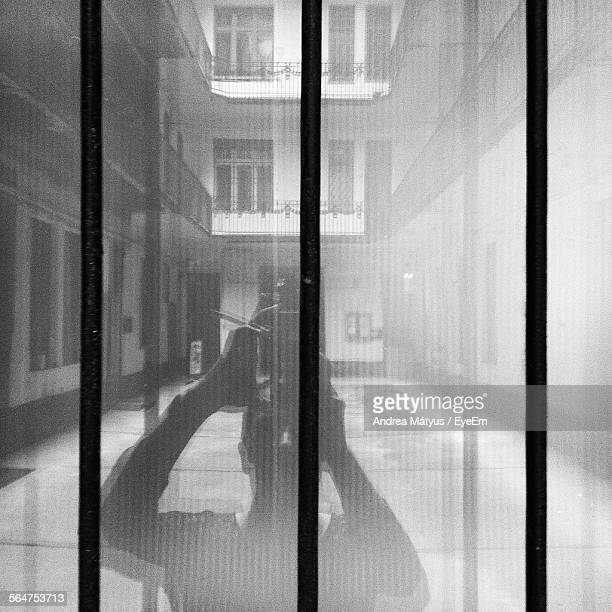 Reflection Of Man Photographing With Mobile Phone In Glass Window