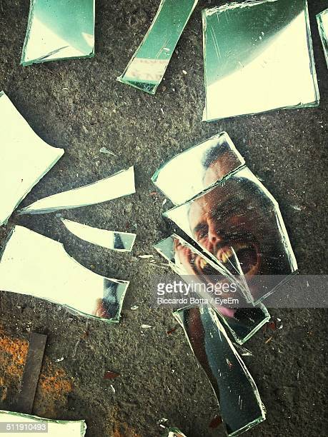 Reflection of man shouting on broken glass