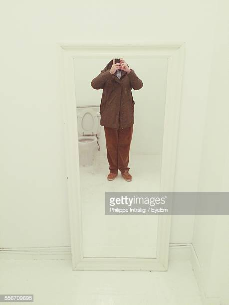 Reflection Of Man Taking Selfie Through Mobile Phone On Bathroom Mirror