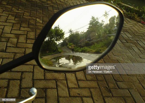 Reflection Of Man Walking On Wet Street On Motorcycle Mirror