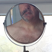 Reflection of man with half shaved face