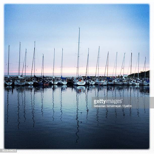 Reflection of moored boats in calm sea