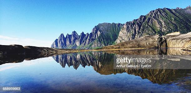 Reflection Of Mountain In Lake Against Clear Blue Sky