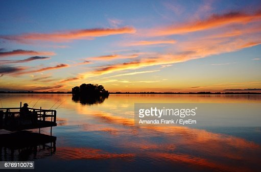 Reflection of orange clouds in river during sunset foto - Castoro immagine a colori ...