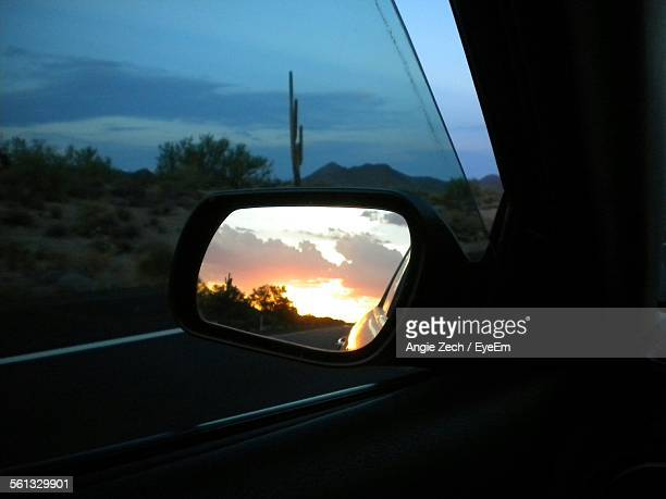 Reflection Of Orange Sky On Side-View Car Mirror At Sunset