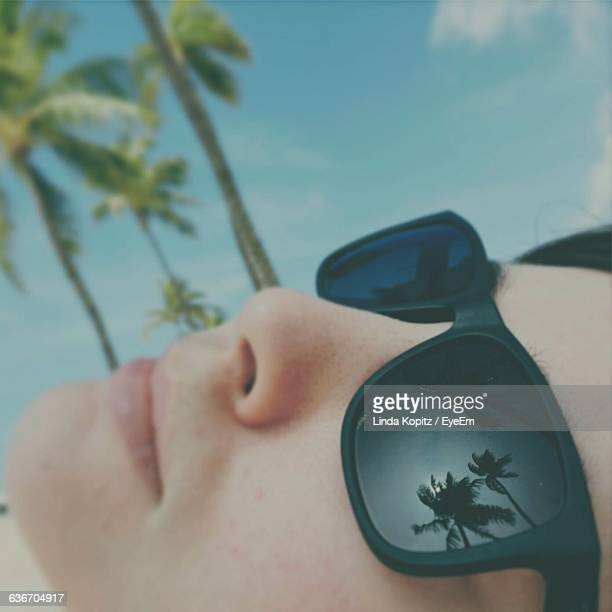 Reflection Of Palm Trees On Woman Sunglass