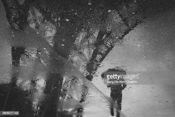 Reflection Of Person And Eiffel Tower In Puddle During Rainy Season