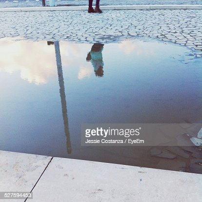 Reflection Of Person On Puddle At Street