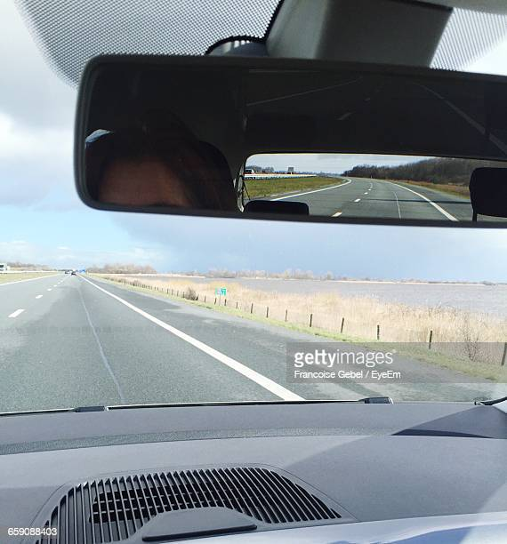 Reflection Of Person On Rear-View Mirror In Car