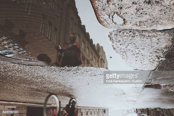 Reflection Of Person Riding Bicycle On Street In Puddle