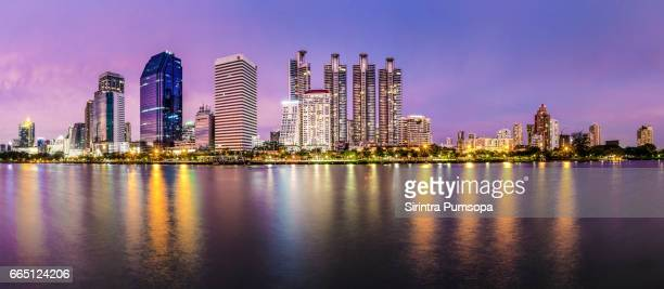 Reflection of public buildings in twilight time at the Benjakiti Park, Bankok, Thailand