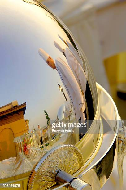 Reflection of restaurant staff in serving tray cover