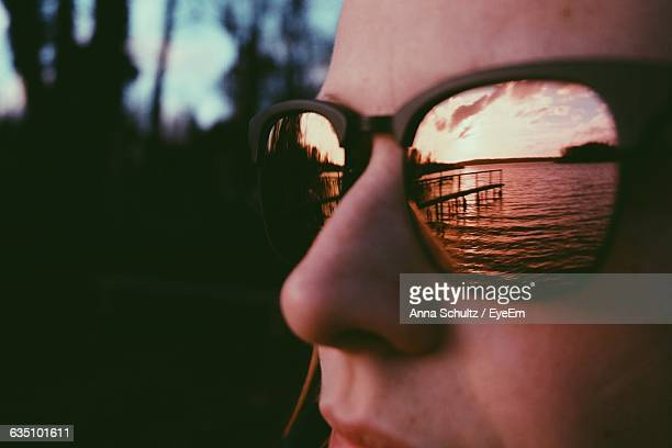 Reflection Of River On Sunglasses Worn By Woman During Sunset