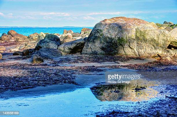 Reflection of rocks on blue water