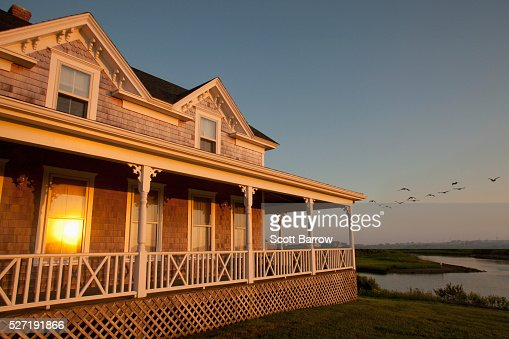 Reflection of setting sun on windows of cottage : Stock Photo