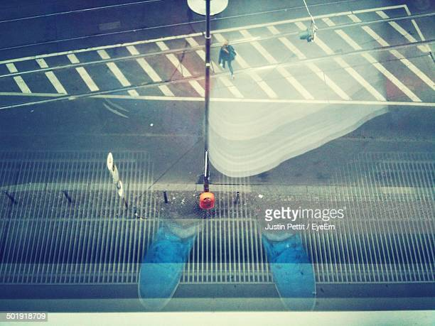 Reflection of shoes as woman cross the empty road
