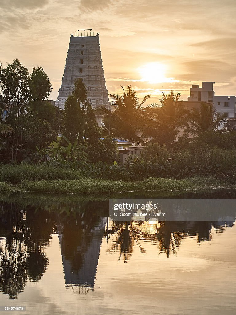 Reflection Of Shri Gopalswamy Temple In Lake Against Sky During Sunset