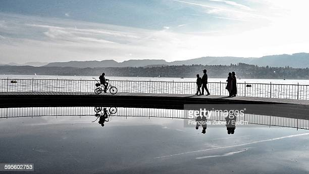 Reflection Of Silhouette People In Lake Against Sky