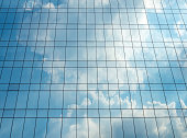 Reflection of blue sky and cloud on glass building. Bright light on glass building, persprctive view.