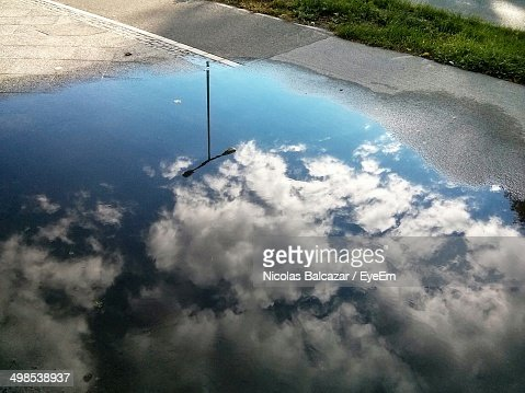 Reflection of sky and clouds in puddle