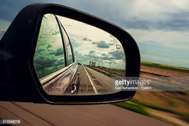 Reflection of street in rear view mirror