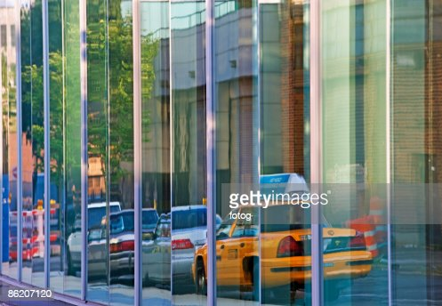 Reflection of taxi cab and cars on building